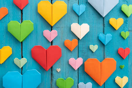 Origami hearts of different colors and sizes in composition on weathered blue wooden background