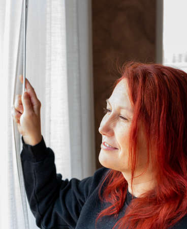 Portrait of middle-aged woman with fair skin and red hair in living room at home 版權商用圖片