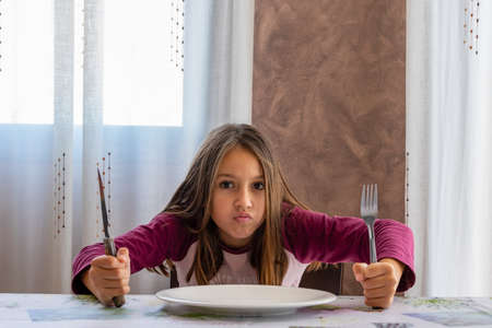 Pretty angry little girl sitting in pajamas waiting for food sitting at the table with cutlery in hand. Anxiety concept Archivio Fotografico