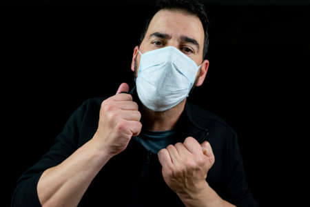 Portrait of man with a beard and a mask to prevent coronavirus wearing a black sweatshirt on a black background in a desperate attitude.Despair concept Imagens