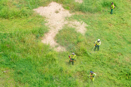 Team of men in work clothes and equipped with professional brush cutters cutting the green grass of an abandoned site