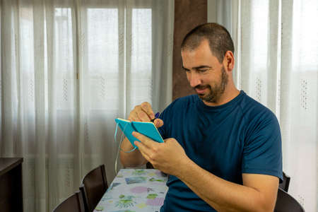Smiling man with beard and short hair pointing notes at his little blue notepad in the living room at home
