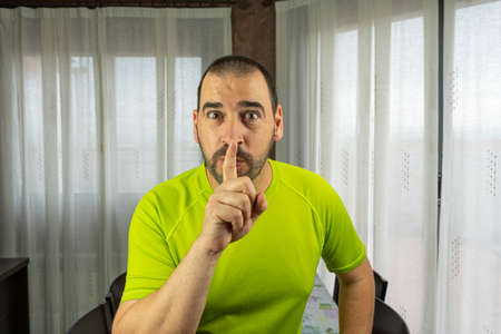 Bearded man with short hair in green shirt making silence symbol in living room at home. Tranquility concept Stock Photo