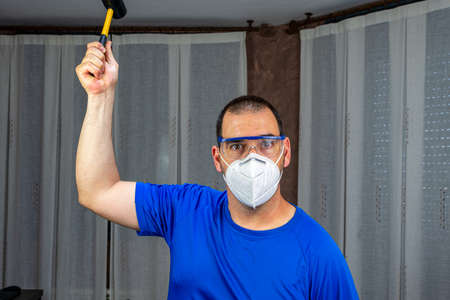 Man with a beard and short hair in a blue shirt and a mask to prevent coronavirus with a rubber hammer in a defiant attitude. Fury concept