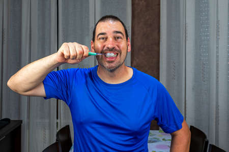 Man with a beard and short hair in a blue shirt brushing his teeth. Hygiene concept