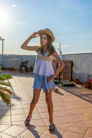Pretty little girl dressed in a white tank top dancing and jumping on the house terrace at sunset. Fun concept