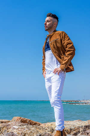 Young man in white pants and modern styling posing on the beach of the Mediterranean Sea in Burriana. Fashion concept Stock fotó