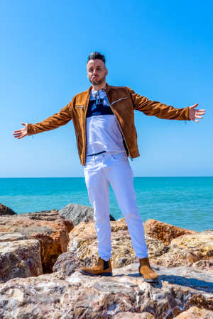 Young man in white pants and modern styling posing on the beach of the Mediterranean Sea in Burriana. Fashion concept Stock fotó - 150297275