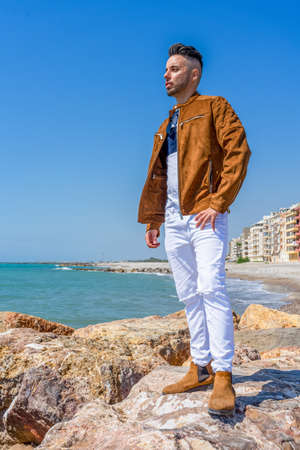 Young man in white pants and modern styling posing on the beach of the Mediterranean Sea in Burriana. Fashion concept Stock fotó - 150297093