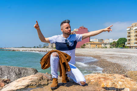 Young man in white pants and modern styling posing on the beach of the Mediterranean Sea in Burriana. Fashion concept