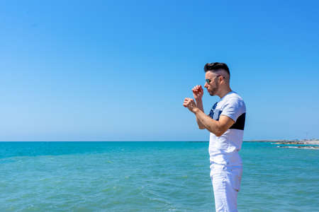 Young man in white pants and modern styling posing on the beach of the Mediterranean Sea in Burriana. Fashion concept Stock fotó - 150297253