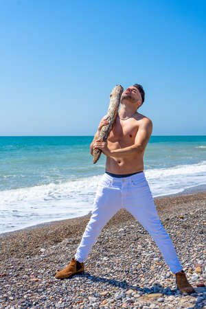Young bearded man posing with a big stick on a beach of the Mediterranean sea. Fun concept