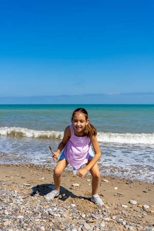 Little girl dressed in pastel colors jumping and playing on the stone and sandy shore of the Mediterranean Sea. Fun concept Banque d'images
