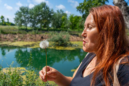 Beautiful middle-age woman with red hair blowing a dandelion in the freshwater pond of Clot de la Mare de Deu in Burriana. Healthy life concept