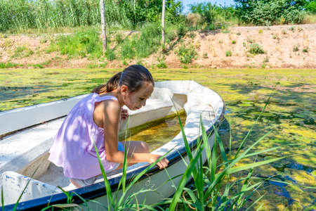Beautiful little girl with her hair up and dressed in pastel colors posing fun riding on a white boat in the freshwater pond of Clot de la Mare de Deu in Burriana. Tranquility concept 免版税图像