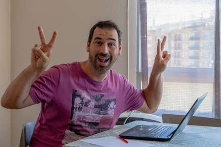 Cheerful bearded man dressed in a purple t-shirt looking at the laptop. Joy concept