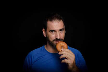 Bearded man dressed in blue t-shirt posing against black background. Fashion concept
