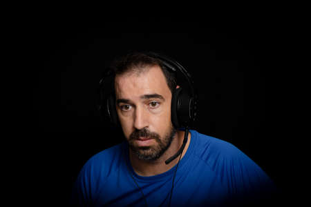 Bearded man dressed in blue t-shirt and with headphones posing on black background. Technology concept