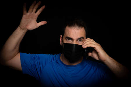 Bearded man dressed in blue t-shirt and with a black mask to protect himself from coronavirus posing against black background. Health concept