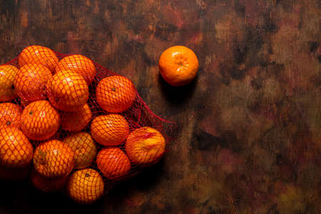 Broken mesh bag of oranges on an old wooden background in shades of brown with oranges scattered over it. Mediterranean diet concept