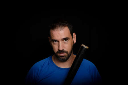 Bearded man dressed in blue t-shirt in defiant pose posing with a baseball bat on a black background.Threat concept