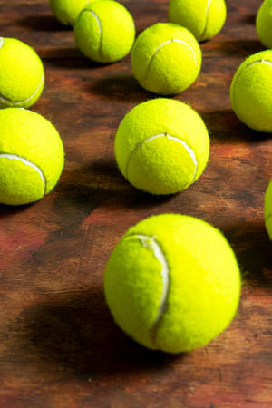 Tennis balls in composition on old wooden background in brown tones. Sport concept Stockfoto