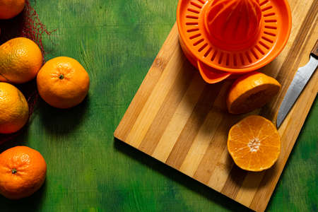 Man's hands making orange juice with a manual juicer on an old wooden background in green tones. Mediterranean diet concept Stockfoto