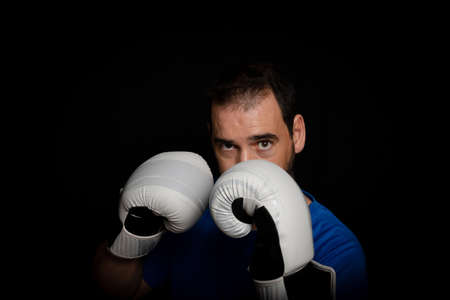 Bearded man dressed in blue t-shirt and with boxing gloves posing on black background. Sport concept
