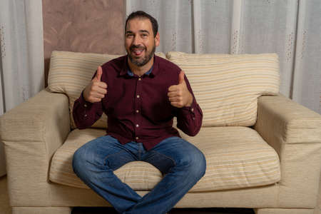 Bearded man with dental braces sitting in armchair with thumbs up sticking out his tongue. Happiness concept