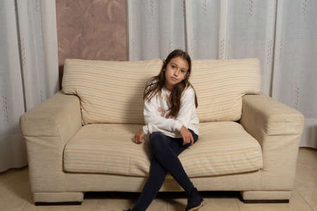 Pretty little girl with long hair posing sitting on the couch at home. Fashion concept