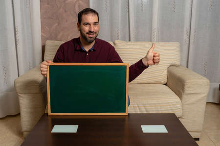 Bearded man sitting on the couch at home with a blackboard with this thumb up. Hope concept