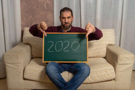 Bearded man sitting on the couch at home with a chalkboard with 2020 written on it and thumbs down in disapproval of a dire year. Negativity concept