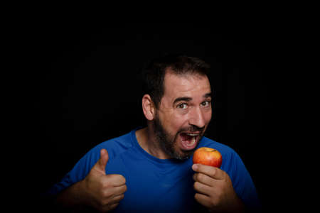 Bearded man dressed in blue t-shirt and holding an apple posing on black background. Healthy diet concept