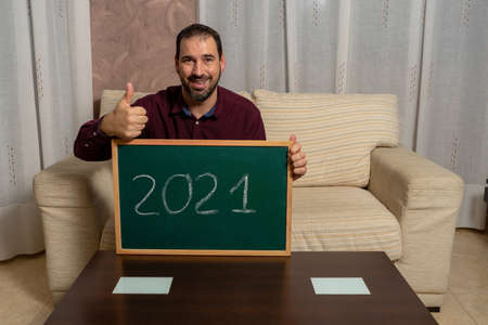 Bearded man sitting on the couch at home with a blackboard with 2010 written on it and his thumbs up in approval of an exciting year. Hope concept