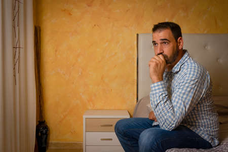 Attractive bearded man depressed and upset in the bedroom at home. Dramatic 30-40 year old lifestyle portrait, handsome man sitting on bed, worried and desperate. Depression concept Stockfoto