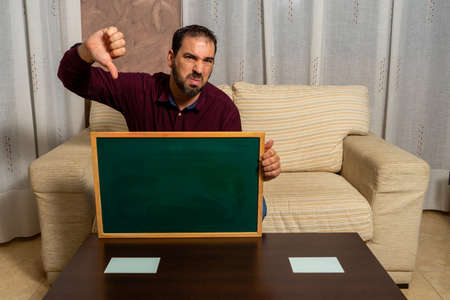 Bearded man sitting on the couch at home with his thumb down. Hopelessness concept