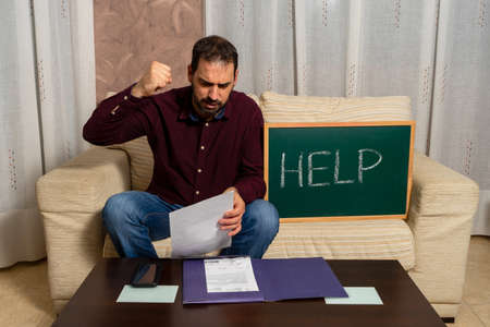 Desperate young man calculating household expenses sitting on the couch and asking for help on a blackboard. Financial problems concept