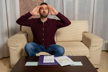 Worried and desperate young man calculating household expenses sitting on the couch at home. Financial problems concept Stockfoto