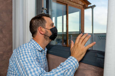 Sick man from coronavirus looking out the window and wearing mask for protection and recovery from illness at home. Desolation concept