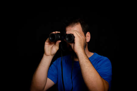 Bearded man dressed in blue t-shirt with binoculars posing against black background. Fashion concept