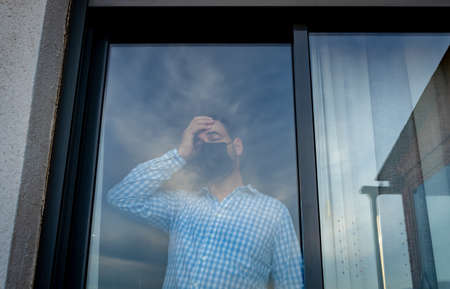Bearded man wearing blue shirt and mask to prevent coronavirus looking out the window with the reflection of the clouds fading