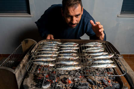 Man cooking a barbecue of fresh sardines on a charcoal barbecue. Healthy food concept