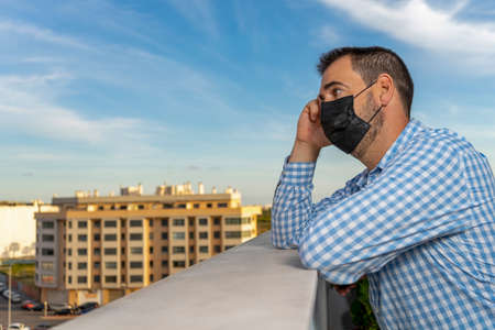Young man on the balcony of the house during the covid-19 outbreak. 40 year old man with mask, worried and tired face looking at the street thoughtful and depressed in quarantine. Isolation concept