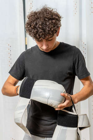Attractive young man with curly hair wearing black t-shirt posing with boxing gloves on white curtains background. Fashion concept
