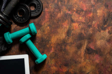 Weights and accessories for exercising at home and a tablet for an online workout.Healthy life concept