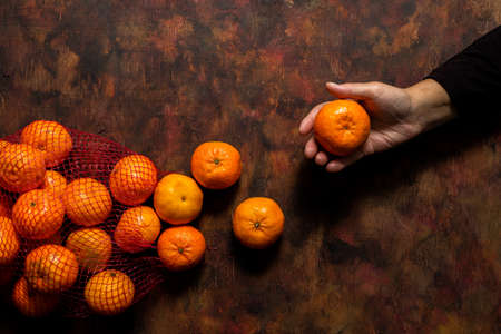 Broken mesh bag of oranges on an old wooden background in shades of brown with oranges scattered over it and a hand grabbing an orange. Mediterranean diet concept Stockfoto