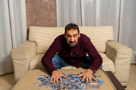 Young man with beard sitting on the couch at home doing puzzle. Entertainment concept