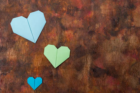 Origami hearts made with colored paper for congratulations on Valentine's Day for couples in love, on an old wooden background in brown tones. Love concept Stockfoto