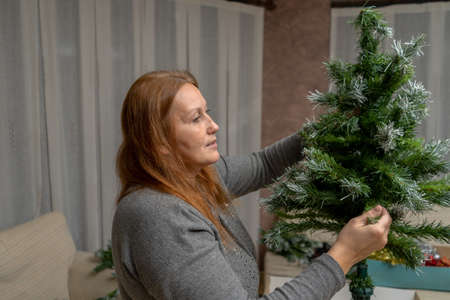 Beautiful middle-aged woman assembling the Christmas tree in her living room. Illusion concept
