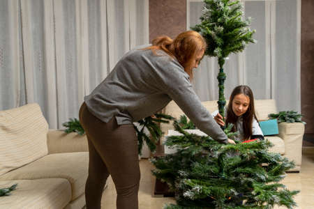Mother and daughter assembling the Christmas tree in their living room. Illusion concept